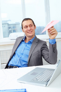 Happy Businessman Playing With Paper Plane In Office