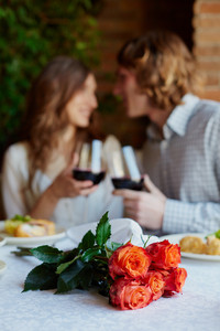 A Bunch Of Red Roses On Served Table And Young Lovers Toasting On Background