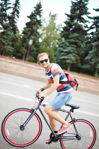 Portrait Of Happy Guy Riding Bicycle In The Park