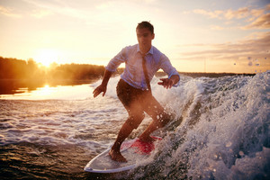 Young Man In Wet Clothes Surfboarding At Summer Resort