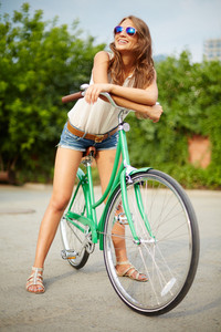 Portrait Of A Pretty Woman On Bicycle Enjoying Summer Day In The Park