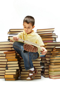 Photo Of Young Boy Reading A Book While Sitting On Books