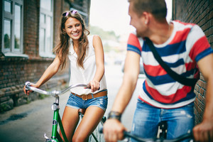 Portrait Of Happy Young Couple On Bicycles Between Two Houses