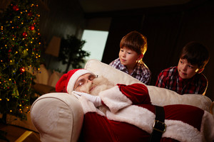 Santa Claus Sleeping On Sofa With Two Boys Looking At Him
