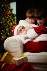 Santa Claus Sleeping With Two Boys Near By And Giftboxes
