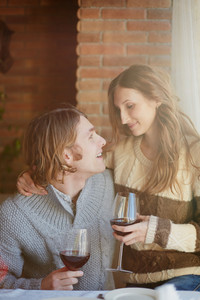 Portrait Of Amorous Young Couple With Red Wine Looking At One Another
