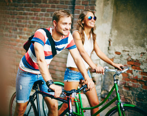 Portrait Of Happy Young Couple On Bicycles