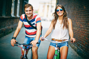 Portrait Of Happy Young Couple On Bicycles On Weekend