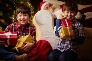 Happy Boys With Giftboxes Looking At Camera On Background Of Sleeping Santa Claus