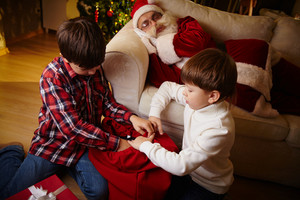 Two Lads Choosing Gifts From Red Sack With Santa Claus Sleeping On Sofa Near By