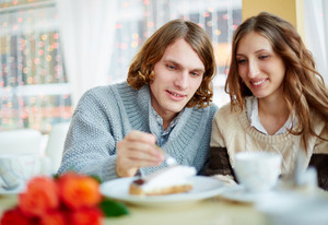Portrait Of Amorous Young Couple Having Dessert In Restaurant