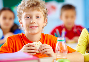 Cheerful Schoolboy Looking At Camera While Having Lunch During Break With His Classmates Behind