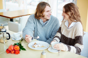 Portrait Of Amorous Young Couple Talking By The Dessert In Restaurant Or Cafe