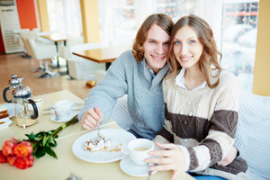 Portrait Of Amorous Young Couple Looking At Camera While Sitting In Cafe