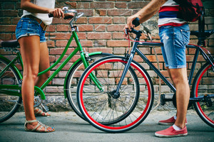Close-up Of Guy And Girl Legs With Bicycles Against Brick Wall