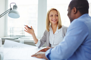 Female Designer Looking At Her Colleague During Interaction At Meeting