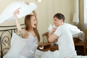 Happy Couple Playing With Pillows In Bed