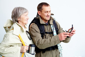 Portrait Of Happy Senior Couple Looking At Compass On Trip