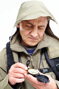 Portrait Of Mature Man Looking At Compass On Trip