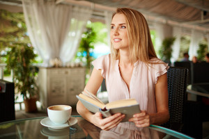 Portrait Of Pensive Girl Reading A Book In Cafe
