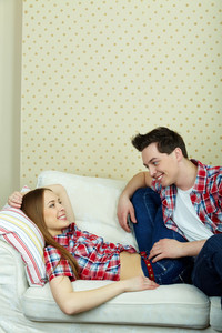 Happy Couple In Casual Clothes Having Rest On Sofa At Home