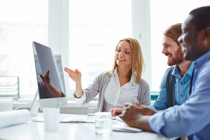 Male Employees Looking At Computer Monitor While Their Female Colleague Presenting New Project