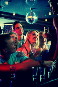 Portrait Of Cheerful Girls And Guys With Cocktails Looking At Their Friend In The Bar