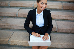 Image Of Young Businesswoman With Laptop Looking At Camera While Networking On Steps Of Building
