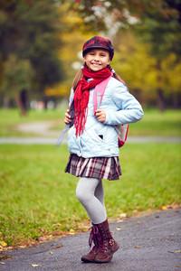 Portrait Of Happy Schoolgirl Standing In Park