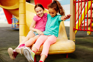 Image Of Two Friendly Girls Having Fun On Playground