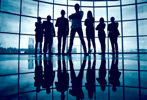 Business Team Standing Against Window With Leader In Front