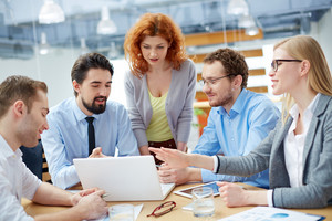Group Of Business Partners Discussing Ideas Upon Computer Project