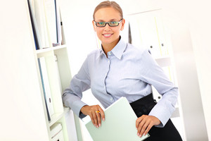 Portrait Of Elegant Office Manager Leaning Against Shelves