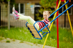Happy Little Girl Looking At Camera While Swinging On Playground Area