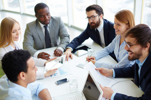 Group Of Business Partners Communicating At Meeting In Office
