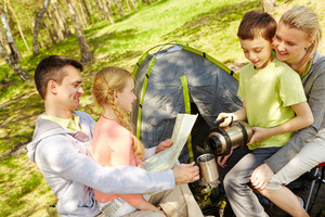 Portrait Of Family Of Travelers Spending Time In Forest With Tent Near By