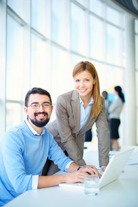 Portrait Of Networking Businessman And Businesswoman On Background Of Their Colleagues