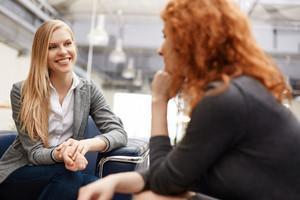 Two Businesswomen Speaking At Meeting Or During Break