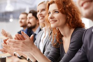 Smiling Female Applauding At Conference Between Her Colleagues