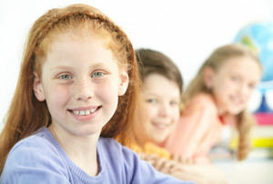 Portrait Of Smart Schoolgirl Looking At Camera With Classmates On Background