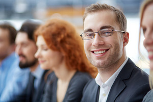 Portrait Of Young Smiling Businessman In Eyeglasses Looking At Camera With His Colleagues On Background