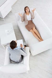 Above View Of Attentive Psychiatrist Listening To Female Patient In Clinic