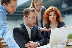 Group Of Business Partners Working With Laptop At Meeting