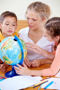 Portrait Of Cute Schoolchildren And Teacher Looking At Globe In Classroom