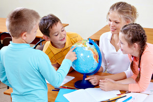 Portrait Of Cute Schoolchildren And Teacher Looking At Globe At Geography Lesson