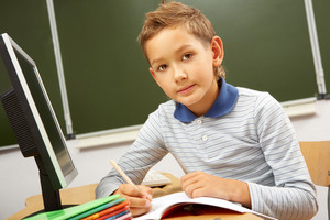 Portrait Of Smart Lad At His Place Looking At Camera In Classroom