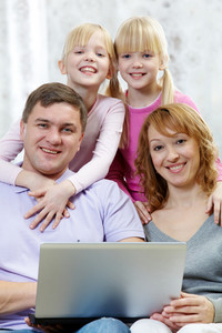 Image Of Happy Family With Laptop Looking At Camera