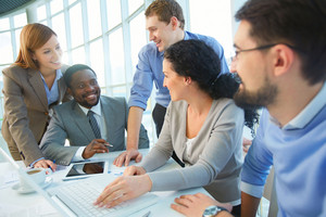 Group Of Cheerful Business Partners Planning Work At Meeting