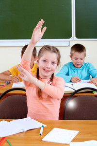 Portrait Of Lovely Girl Raising Hand At Workplace With Schoolboys On Background