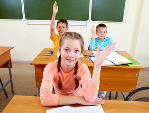 Portrait Of Lovely Girl And Two Schoolboys On Background Raising Hands At Workplace